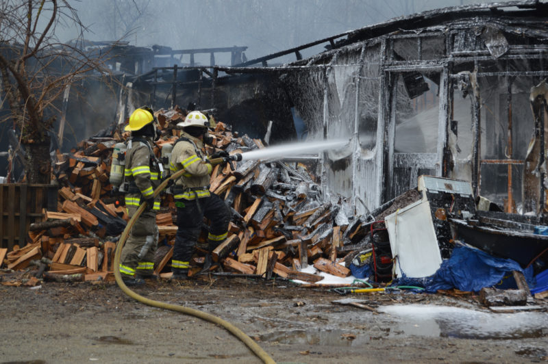 Firefighters use foam to suppress remaining hot spots after a fire destroyed a house on Lessner Road in Damariscotta. The fire has been ruled accidental by the Maine State Fire Marshal's Office. (Maia Zewert photo)