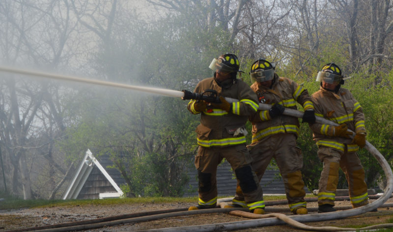 Alna firefighters work on scene at 38 South Dyer Neck Road in Newcastle on Thursday afternoon, May 12. The Newcastle, Damariscotta, Nobleboro, Wiscasset, Edgecomb, Alna, Boothbay, and Bristol departments either responded to the scene or provided station coverage. (Maia Zewert photo)