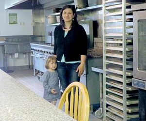 Owner Milva Smith with her daughter Mila, 3, in the Food Forge kitchen. The kitchen is equipped with a 12-burner gas stove, convection oven, three-bay sink, fryers, and much more. (Haley Bascom photo)
