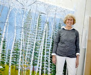 "Painter Jane Dahmen stands in her Newcastle home-studio before ""Spring Birches and Evergreens,"" a 72-by-72-inch acrylic two-panel painting created on doors. Dahmen's ""Four Seasons"" art show will open at the Portland Art Gallery on Thursday, June 2. (Christine LaPado-Breglia photo)"