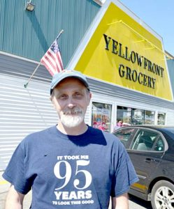 "Yellowfront Grocery owner Jeff Pierce stands in front of the store, which is celebrating its 95th anniversary. His shirt - a gift from a customer - reads ""It took me 95 years to look this good."" (Maia Zewert photo)"