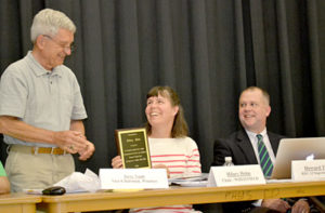 From left: RSU 12 Vice Chair Jerry Nault presents a plaque to outgoing Chair Hilary Holm at her final RSU 12 Board of Directors meeting Thursday, June 16 as Superintendent Howard Tuttle looks on. (Abigail Adams photo)