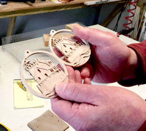 Jack Hanson compares two ornaments recently cut by a computer numeric control machine in his Newcastle home. After an ornament is cut, Hanson and his wife, Macky, sand the ornament to remove any rough sections. (Maia Zewert photo)