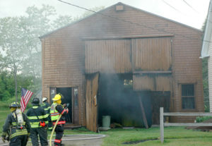 Firefighters were able to prevent a boathouse fire from spreading to a house only feet away, at right. (Alexander Violo photo)