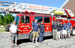 From left: Assistant Fire Chief Nick Merry, James Pray, Kevin Brewer, Kyle Viele, Devin Grover, Steven Smith, Capt. Nick Grover, Brycson Grover, and Chris Cossette stand in front of Ladder 1 on Monday, July 4. The truck is back in service after nearly a year away for repairs. (Charlotte Boynton photo)
