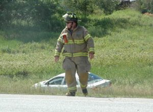 A Nobleboro firefighter works at the scene of a three-vehicle accident on Route 1 the afternoon of Monday, July 11. One of the three vehicles is in the ditch behind him. (Alexander Violo photo)