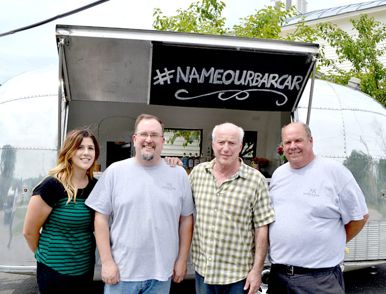 """From left: Leslie Lorentzen, Jed Weiss, Warren Storch, and Todd Maurer stand in front of Stone Cove Catering's new addition, a 1963 Airstream GlobeTrotter """"bar car."""" (Maia Zewert photo)"""
