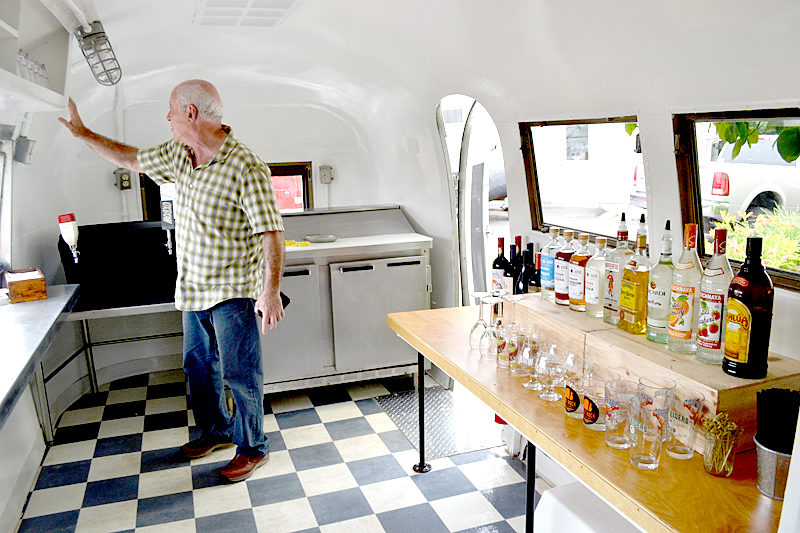 The Walpole Barn owner Warren Storch inspects the interior of a 1963 Airstream GlobeTrotter that Stone Cove Catering recently renovated into a bar car. (Maia Zewert photo)