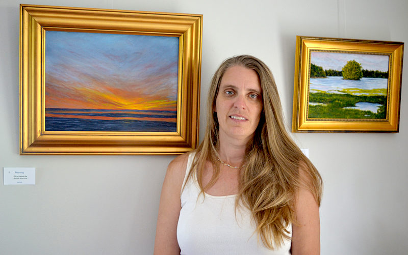 "Pemaquid Watershed Association Executive Director Jennifer Hicks is flanked by two of Helen Warner's oil paintings that are part of Warner's show, ""Our Natural World,"" currently hanging on the walls of the PWA's new office at 584 Main St., Damariscotta. At left is ""Morning""; on the right is ""Looking Upstream."" (Christine LaPado-Breglia photo)"
