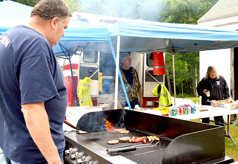 Dresden Assistant Fire Chief Ron Theriault flips a burger and cooks hot dogs to help raise money for the Dresden Fire Department. (Haley Bascom photo)