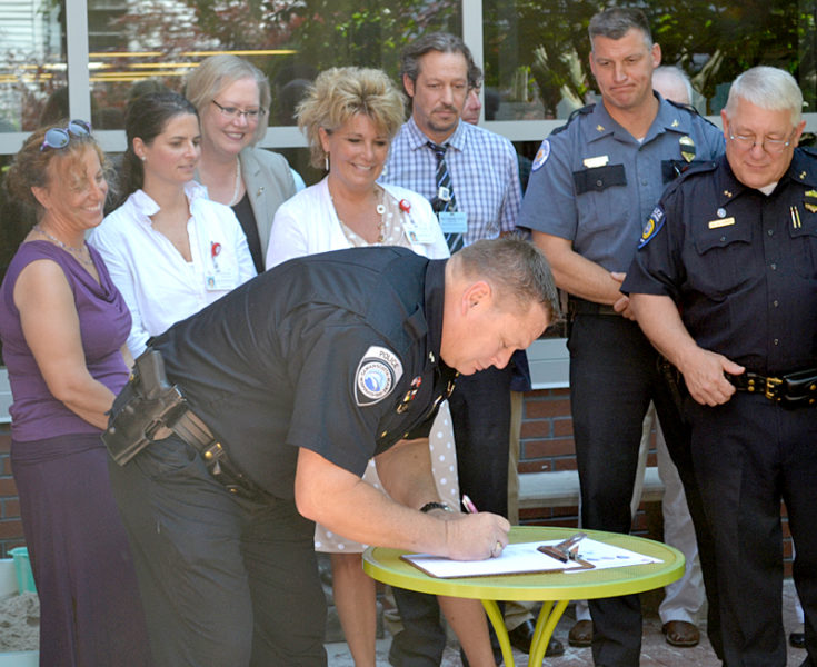 Damariscotta Police Chief Ron Young signs a memorandum of understanding for the Lincoln County Recovery Collaborative as fellow police chiefs and stakeholders from LincolnHealth, Mid Coast Hospital, and the CLC YMCA look on Friday, July 15. (Abigail Adams photo)