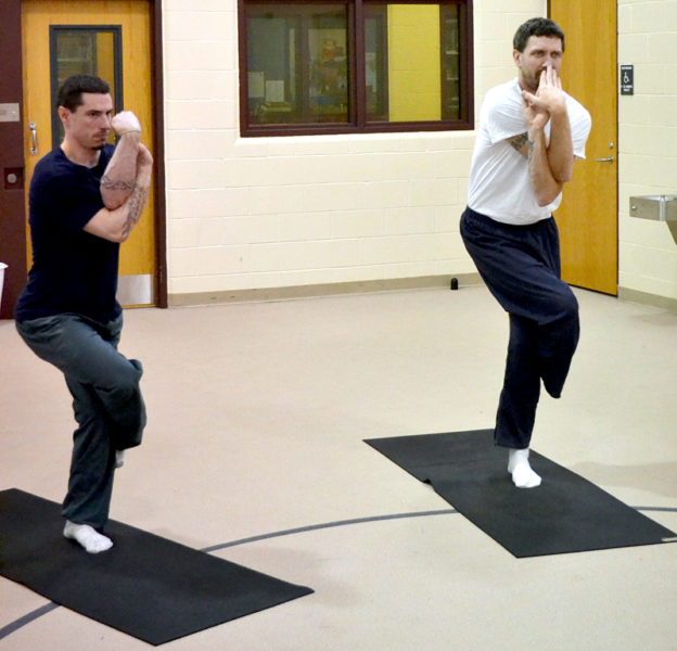 Ben Foster (left) and Jason DuRoss go into the eagle pose during a yoga class at Two Bridges Regional Jail on Thursday, July 14. (Abigail Adams photo)