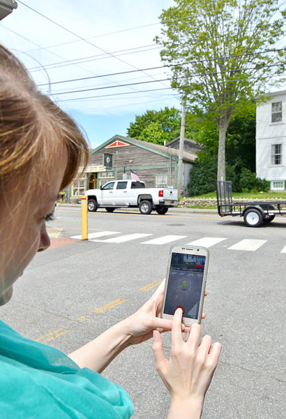 Pokemon Go enthusiast Amber Clark, of Newcastle, attempts to capture a Pokemon called Bellsprout by throwing a Poke Ball at it across the street from S. Fernald's Country Store in downtown Damariscotta on Monday, July 18. (Haley Bascom photo)