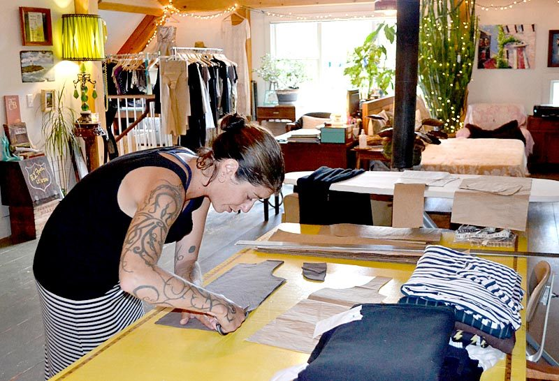 Katrina Kelley, owner and seamstress of Amphitrite Studio Clothing Co., cuts a tank top for her clothing line in her Newcastle home. Kelley uses natural and organic fibers for her women's clothing line, including linen, cotton, and bamboo. (Maia Zewert photo)