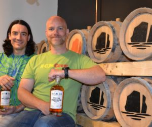 Split Rock Distilling co-founders Topher Mallory (left) and Matt Page display bottles of the distillery's bourbon, one of five products available during the business's soft opening on the holiday weekend. (Maia Zewert photo)