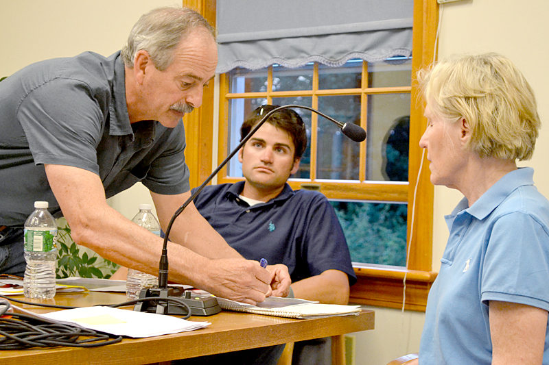 Mook Sea Farms Inc. owner Bill Mook explains the boundary of his proposed aquaculture lease to Sigrid Sproul while Jeff Auger, farm manager for Mook Sea Farms, looks on during a hearing at the South Bristol town office Wednesday, July 13. (Maia Zewert photo)