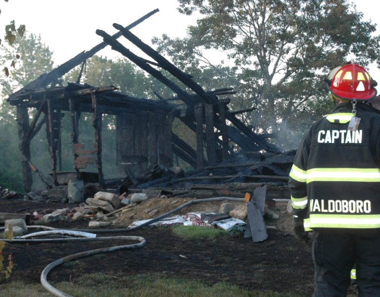 A Waldoboro firefighter looks on as crews finish up work at the scene of a house fire at 99 Atlantic Highway. There were no injuries, but the home was a total loss, according to Waldoboro Assistant Fire Chief William Maxwell. (Alexander Violo photo)