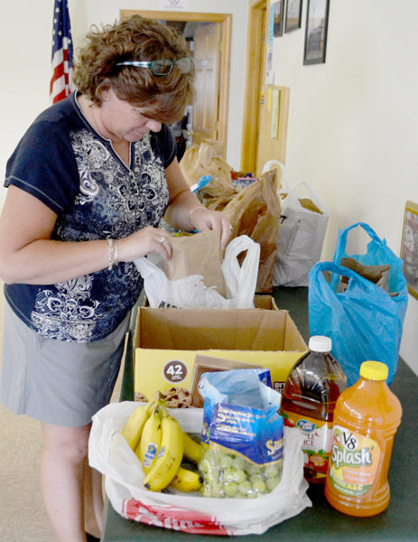 Caring for Kids President Jenny Pendleton inspects a food package prior to delivery. The nonprofit is providing weekly packages of food to 16 families in Bristol throughout the summer. (Maia Zewert photo)