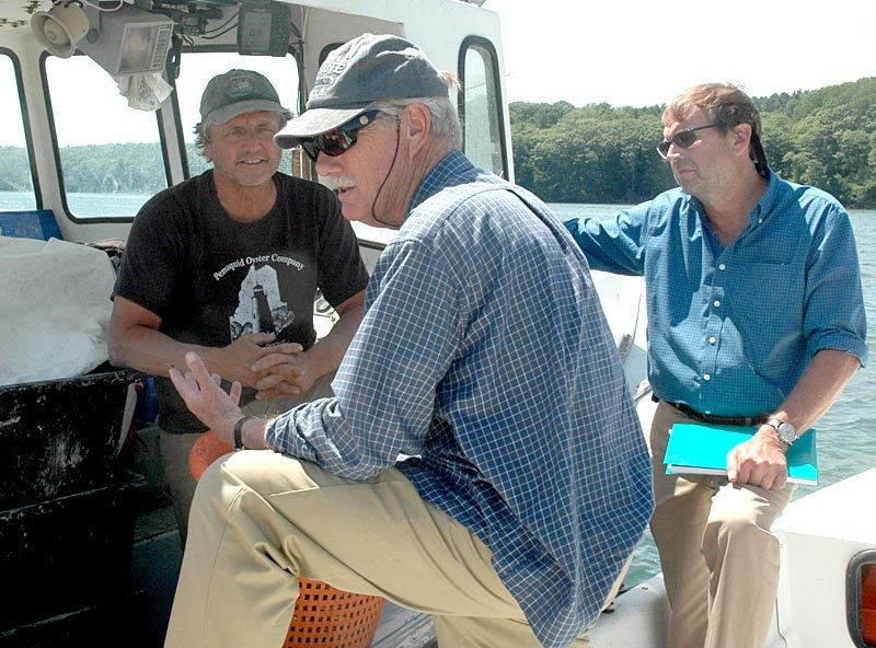 From left: Pemaquid Oyster Co. Inc. President Carter Newell, U.S. Sen. Angus King, and Maine Aquaculture Association Executive Director Sebastian Belle discuss the day-to-day operations of Newell's company on the Damariscotta River. (Alexander Violo photo)