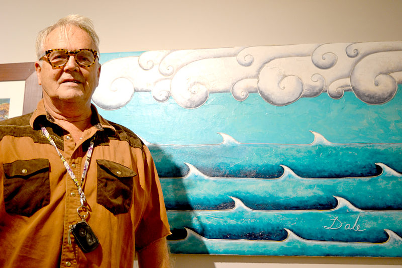 "Dale Dapkins stands before his whimsical acrylic painting ""Doric Clouds"" at the recent opening reception for the ""Rock 'n' Wave"" art show at the Kefauver Studio & Gallery in Damariscotta. (Christine LaPado-Breglia photo)"