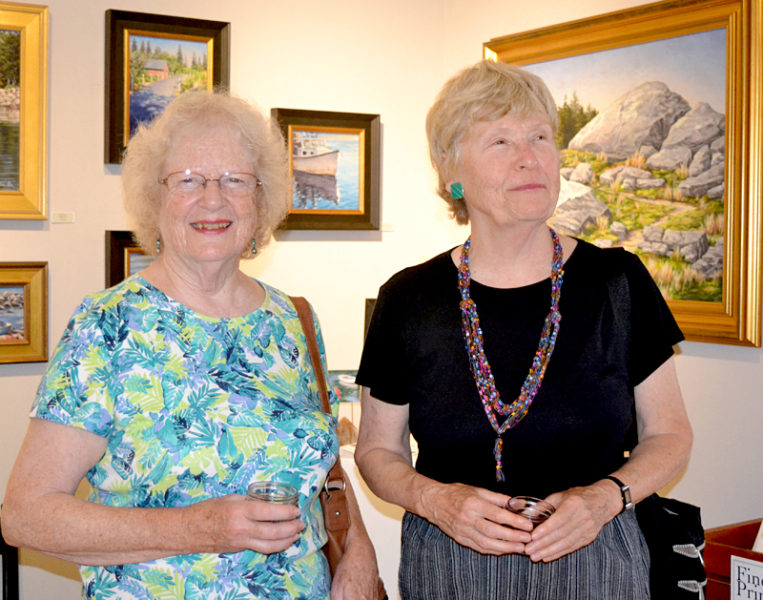 "Bristol artist Judy Nixon (left) and artist Jane Bowman, of New Harbor, sip wine and take in the profusion of art at the Saturday, Aug. 6 opening reception for the ""Rock 'n' Wave"" art show at the Kefauver Studio & Gallery in Damariscotta. Both Nixon and Bowman have artwork in the current show, which runs through Aug. 28. (Christine LaPado-Breglia photo)"
