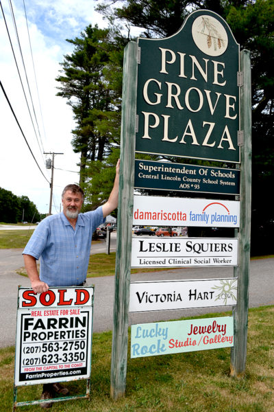 Farrin Properties owner Wayne Farrin stands next to the sign for Pine Grove Plaza at 767 Main St. in Damariscotta. Farrin Properties recently purchased the 23-acre property, which includes the office space, an attached house and garage, and a second garage. (Maia Zewert photo)