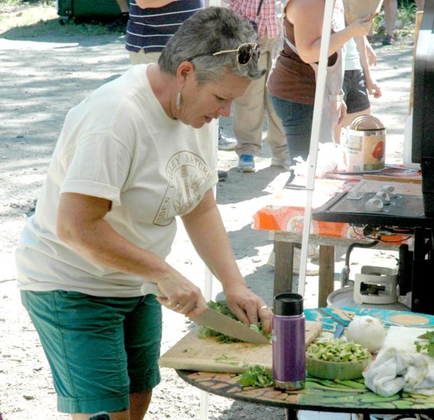 Midcoast Conservancy Communications and Membership Manager Ali Stevenson prepares fresh food at the Live Edge Music Festival. (Alexander Violo photo)