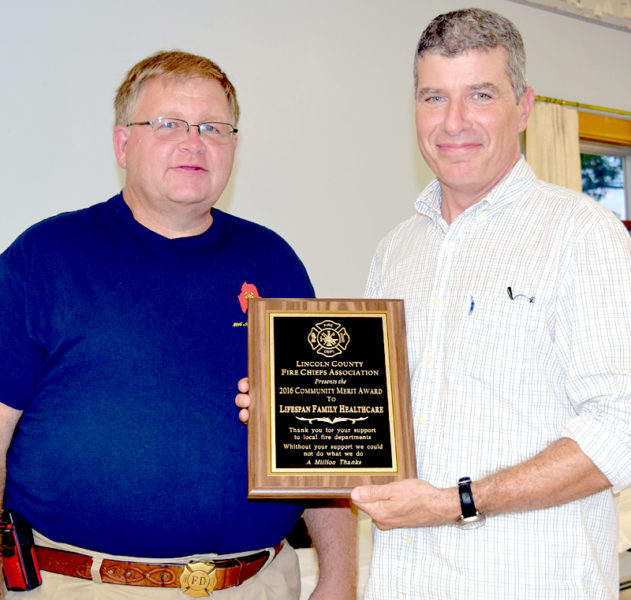 Lincoln County Fire Chiefs Association Vice President Walter Morris (left) presents the association's Community Merit Award for Lifespan Family Healthcare to Dr. Michael Clark. (J.W. Oliver photo)