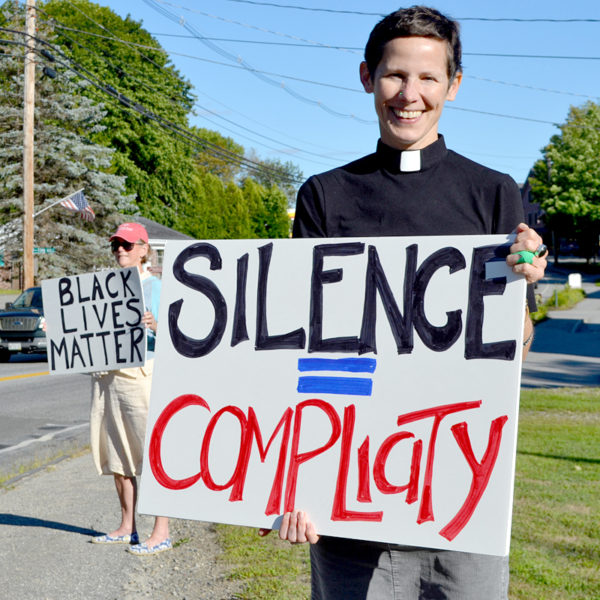 The Rev. Erika Hewitt, of the Midcoast Unitarian Universalist Fellowship, and Julia Fitz-Randolph (left) hold signs during a vigil to protest racism at Veterans Memorial Park in Newcastle on Monday, Aug. 22. (Maia Zewert photo)