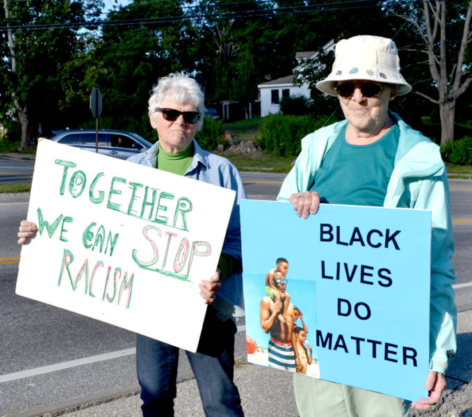 """From left: Bobsy Thompson, of Edgecomb, and Suzanne Hedrick, of Nobleboro, participate in a weekly vigil at Veterans Memorial Park in Newcastle to protest racism. """"We're trying to stop it and make people more aware about it,"""" Thompson said. (Maia Zewert photo)"""