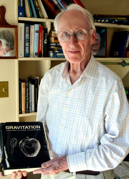 """Charles Misner holds a copy of """"Gravitation,"""" the physics textbook he wrote with Kip Thorne and John Wheeler at his home in South Bristol in the early 1970s. Misner is a renowned physicist who has studied general relativity theory for the past 50 years. (Maia Zewert photo)"""