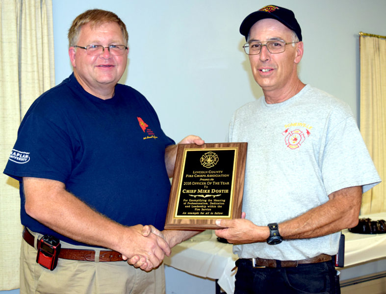 Jefferson Fire Chief and Lincoln County Fire Chiefs Association Vice President Walter Morris (left) presents the association's Officer of the Year Award to Somerville Fire Chief Mike Dostie. (J.W. Oliver photo)