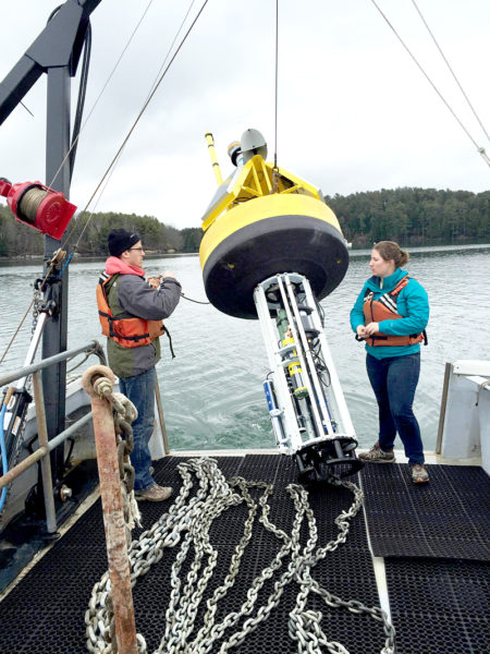 Matthew Gray and Katie Coupland deploy a buoy. Gray is a postdoctoral research associate and Coupland is a doctoral candidate in oceanography; both are based at the University of Maine Darling Marine Center in Walpole.