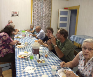 Community members enjoy a potluck supper before the 63 card game.