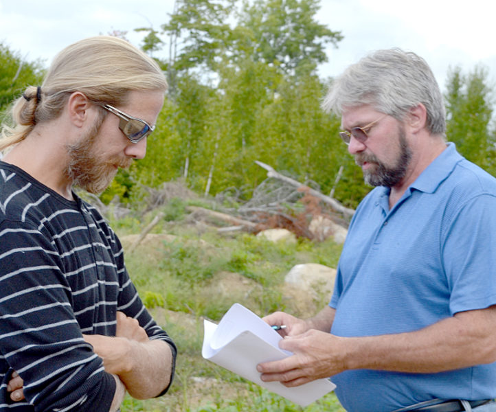 Brian Fifield (left) looks on as Dresden Planning Board Chairman Jeff Pierce reviews his permit application during a site walk at Fifield's property in Dresden on Tuesday, Sept. 6. (Maia Zewert photo)