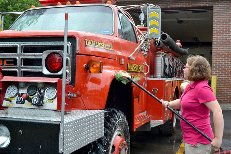 Lincoln Academy sophomore Crystal Miller scrubs a Damariscotta fire truck as part of Lincoln Academy's Sophomore Service Day on Wednesday, Aug. 31. (Maia Zewert photo)