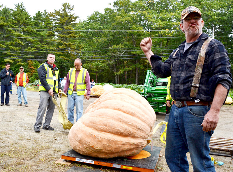 Damariscotta Pumpkinfest co-founder Bill Clark (right) celebrates as he learns the weight of Curt Crosby's pumpkin during the weigh-off at Pinkham's Plantation on Sunday, Oct. 2. Crosby's pumpkin weighed 1,155 pounds, a personal best. (Maia Zewert photo)