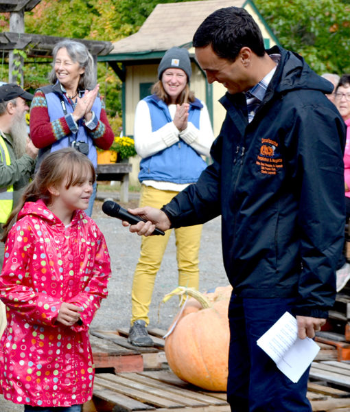 Megan Herrick, of Washington, answers a question from master of ceremonies Charlie Lopresti during the Damariscotta Pumpkinfest's annual weigh-off at Pinkham's Plantation in Damariscotta on Sunday, Oct. 2. Herrick said it was her first year competing in the weigh-off and she plans to grow another pumpkin next year. (Maia Zewert photo)
