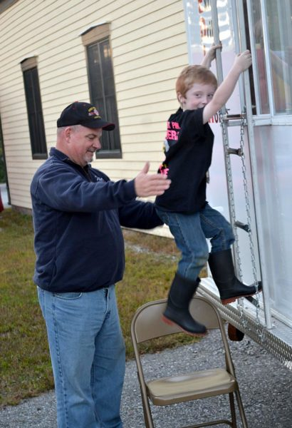 Dresden firefighter Ike Heffron helps Carver Spicer down a ladder after Spicer went through the safety and education smoke trailer at the department's open house Wednesday, Oct. 5. (Abigail Adams photo)