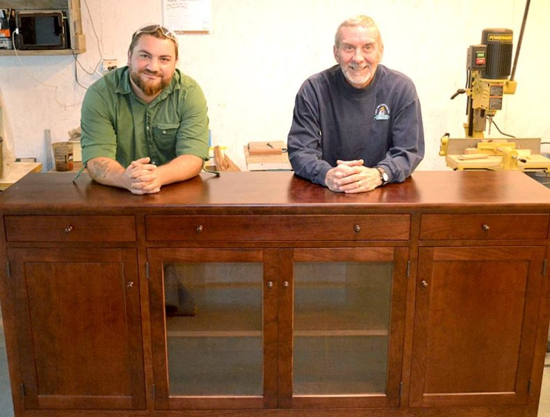 Jesse Daiute (left) and Chris Erickson stand in their Edgecomb workshop with one of their custom pieces of furniture on Thursday, Sept. 29. (Abigail Adams photo)