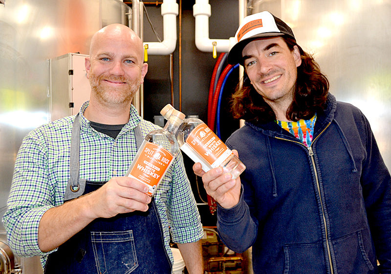 Split Rock Distilling co-founders Matt Page (left) and Topher Mallory display bottles of white whiskey, the newest spirit in the organic distillery's line. The Newcastle business will celebrate its grand opening throughout Columbus Day weekend, Oct. 7-9. (Maia Zewert photo)