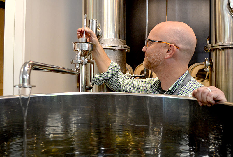 Split Rock Distilling co-founder Matt Page checks the temperature of the still Monday, Oct. 3. (Maia Zewert photo)