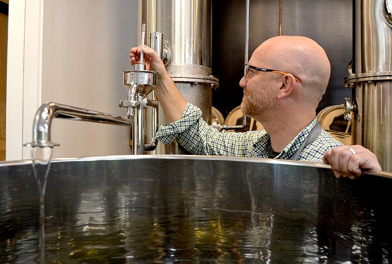 Split Rock Distilling co-founder Matt Page checks the temperature of the still Monday, Oct. 3. (Maia Zewert photo)