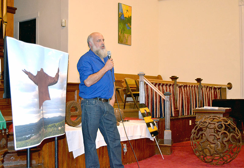 "Metal artist Jay Sawyer, a graduate of Medomak Valley High School in Waldoboro, gives a presentation titled ""Making New Art from Old Items"" as the Waldoborough Historical Society's final program of the year on Wednesday, Oct. 12 at the Broad Bay Congregational United Church of Christ in Waldoboro. He is surrounded by examples of his work, including a large photograph of his metal sculpture ""The Maestro;"" a yellow-and-black-striped metal sculpture called ""Bumble B""; and a 29-inch sphere made of used horseshoes salvaged from a horse farm in Virginia. (Christine LaPado-Breglia photo)"