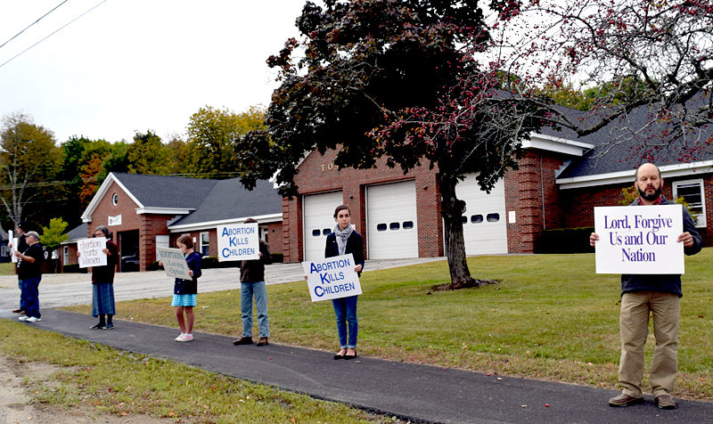 "Participants in a Life Chain event hold signs reading ""abortion hurts women,"" ""abortion kills children,"" ""adoption: the loving option,"" and ""Lord, forgive us and our nation"" in Wiscasset on Sunday, Oct. 2. (J.W. Oliver photo)"