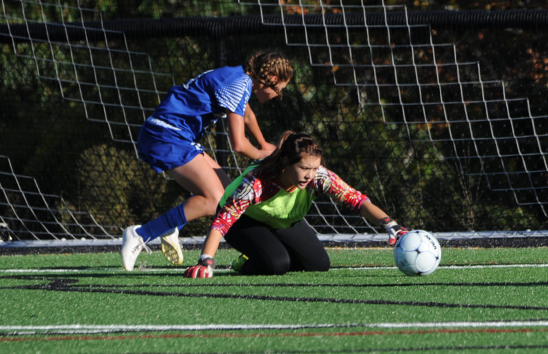Lincoln Academy goal keeper Christine Hilton makes the save after a colision with an Erskine Academy player. (Paula Roberts photo)