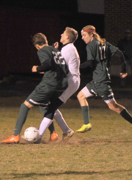 Grant Hefler gets an elbow to the midsection from Waynflete defender Miles Upton. (Paula Roberts photo)