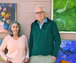 Patti Bradley and Winslow Myers stand before several of Bradley's oil paintings in their shared art studio in their Bristol home. (Christine LaPado-Breglia photo)