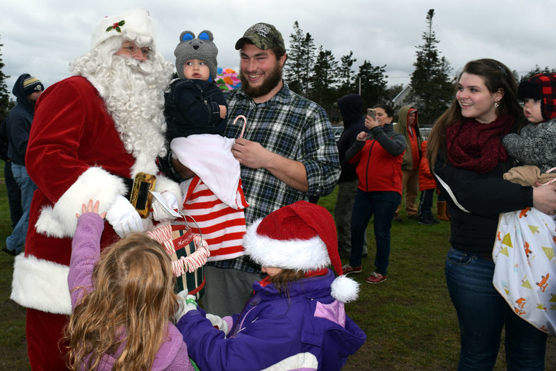 Santa Claus draws curious looks from a couple of babies as other children try to attract his attention during his visit to Pemaquid Point Lighthouse Park on Sunday, Nov. 27. (J.W. Oliver photo)