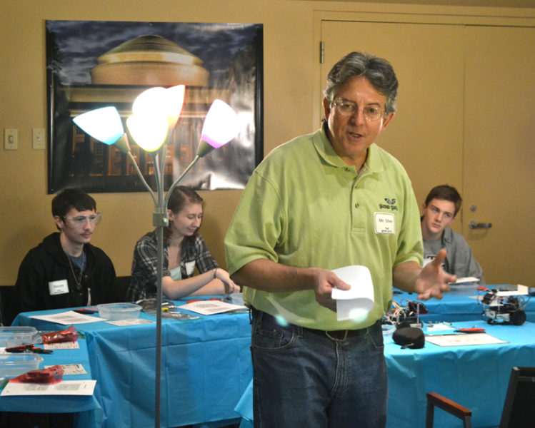 Gizmo Garden Technical Director Bill Silver speaks to a group of students and community members assembling robots at Skidompha Library in Damariscotta on Sunday, Nov. 20. Berthold Horn, a professor at the Massachusetts Institute of Technology, will use the robots for his research on traffic flow. (Maia Zewert photo)
